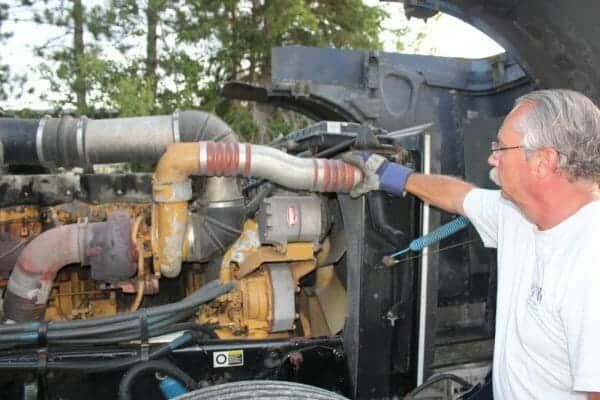 Trucker Fixing Caterpillar Diesel Engine