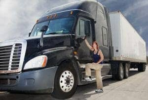 Woman Truck Driver Getting into Black Big Rig