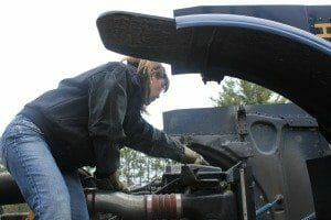 Female trucker fixing engine