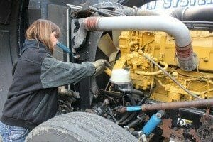 Lady trucker fixing big rig