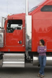 Female Trucker with Red Big Rig - CDL Schools in Maine