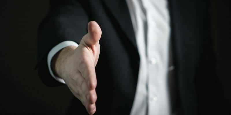 Salesman extending hand to shake on a deal