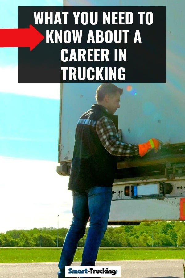 Truck driver opening doors of trailer by roadside.
