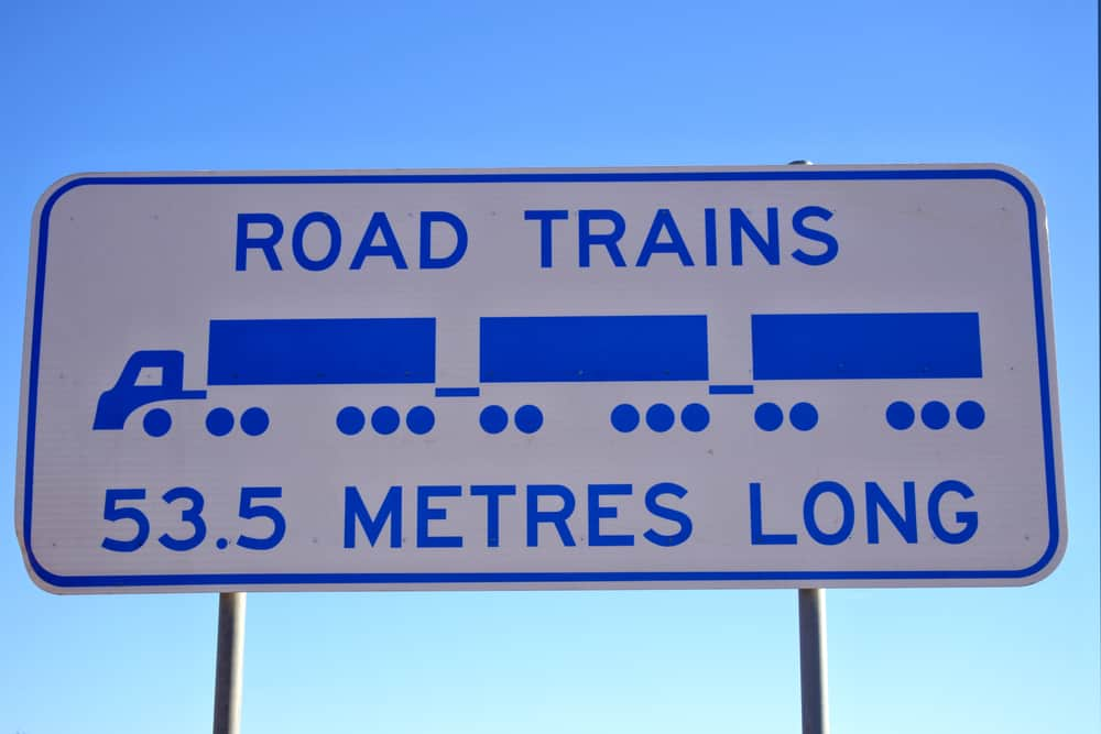 Road Trains Sign in against blue sky in central Australia outback.