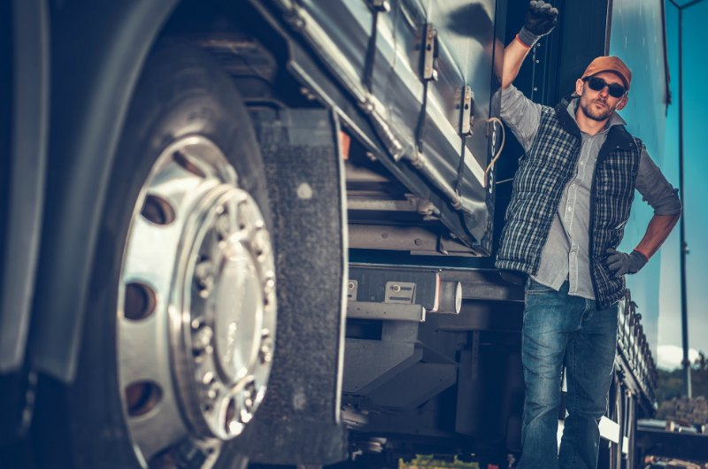 Truck driver leaning on big rig truck