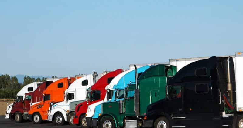 Row of coloured semi trucks with blue sky background